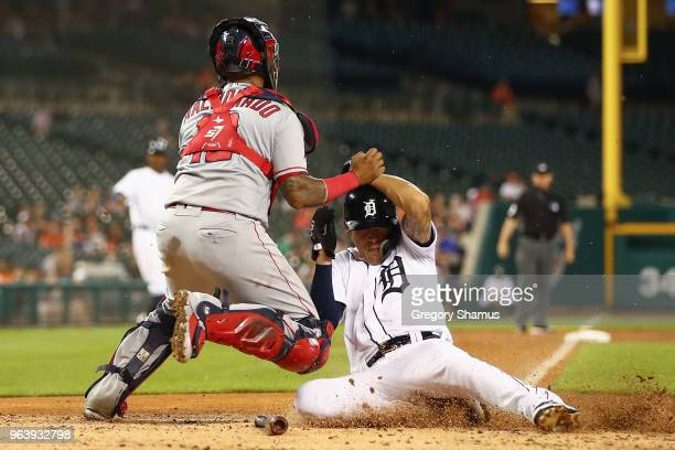 JaCoby Jones of the Detroit Tigers slides under the tag of Martin Maldonado of the Los Angeles Angels to score in the fifth inning at Comerica Park...