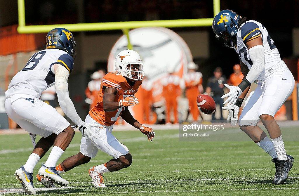 Jacorey Warrick #11 of the Texas Longhorns looses the ball as Marvin Gross #18 and Sean Walters #27 of the West Virginia Mountaineers at Darrell K Royal -Texas Memorial Stadium on November 12, 2016 in Austin. Texas.