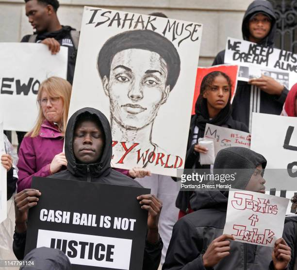 Jacque Francis holds a sign saying cash bail is not justice while standing with over 200 people on the steps of City Hall in Portland on Tuesday,...