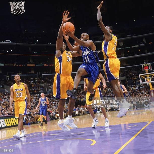 Jacque Vaughn of the Orlando Magic goes for the basket in between Shaquille O'Neal and Kareem Rush of the Los Angeles Lakers at Staples Center on...