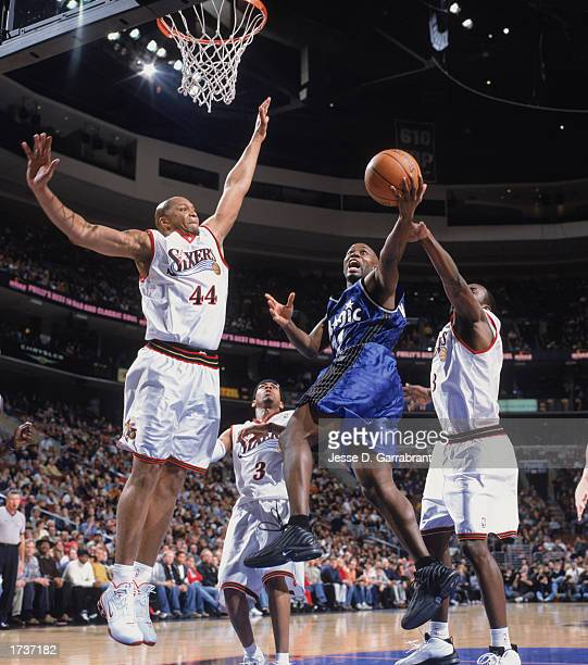 Jacque Vaughn of the Orlando Magic makes a layup between Aaron McKie and Derrick Coleman of the Philadelphia 76ers during the game at First Union...