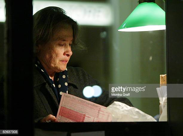 Jacquelin Jensen fills out her tax forms as she is seen through the window of the James A Farley post office where hundreds of people are gathered to...