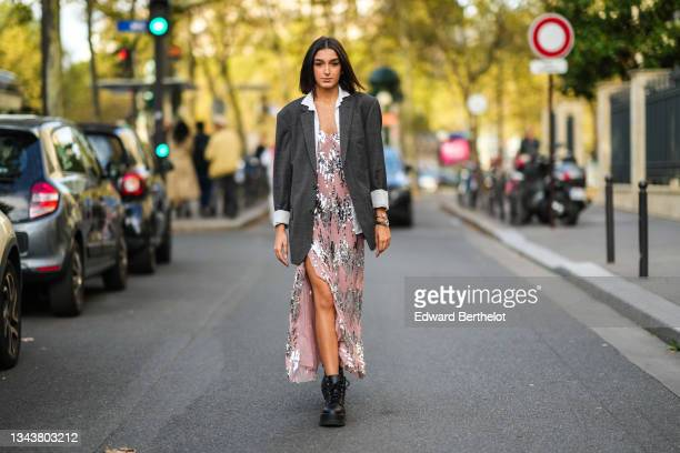 Jacqueline Barth wears earrings, a white open shirt, a dark gray long blazer jacket, a pale pink with embroidered sequined pattern V-neck dress, a...