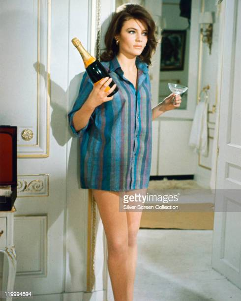 Jacqueline Bisset, British actress, wearing a shirt with vertical stripes, and holding a bottle of champagne and a champagne coupe, in a publicity...