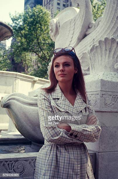 Jacqueline Bisset in a plaid jacket standing by a sculpture; circa 1970; New York.