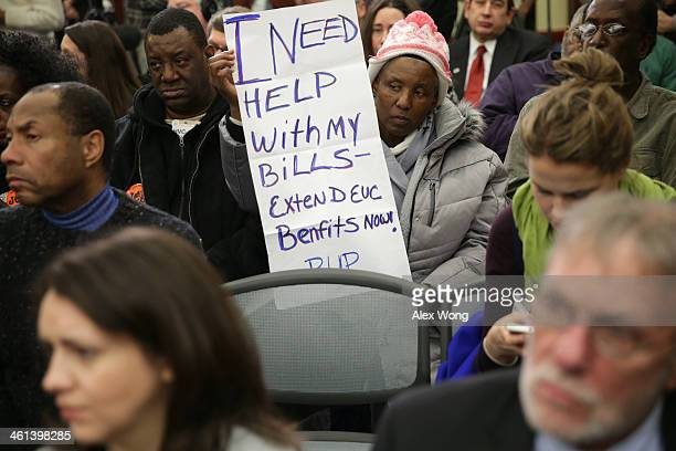 Jacqueline Chapman of Philadelphia holds a poster during a news conference January 8 2014 on Capitol Hill in Washington DC US House Minority Leader...