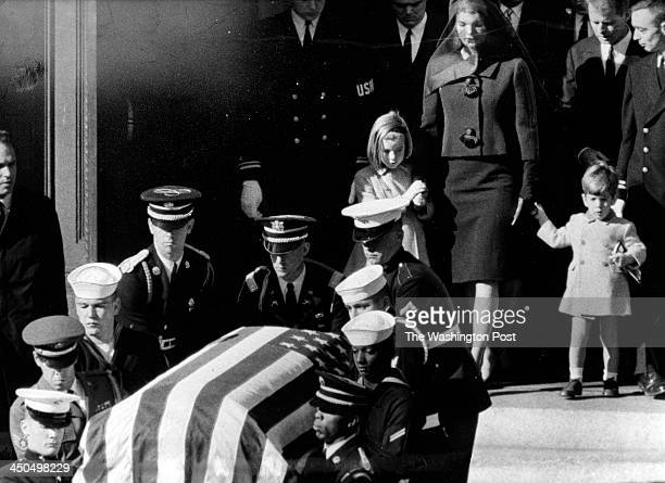 Jacqueline Kennedy and her children, Caroline and John follow the flag-draped casket being carried from St. Matthew's Cathedral by a military honor...