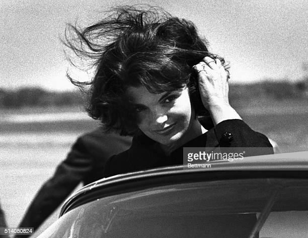 Jacqueline Kennedy brushes her wind-blown hair out of her eyes as she enters a car at Barnstable Airport in Hyannis. She arrived to appear in an...