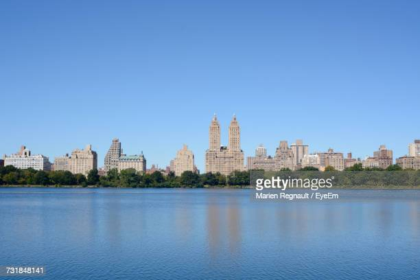 jacqueline kennedy onassis reservoir at central park against clear blue sky in city - central park reservoir stock pictures, royalty-free photos & images