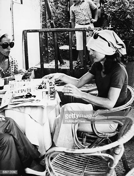 Jacqueline Kennedy Onassis , the wife of Greek shipping magnate Aristotle Onassis and former US first lady, reaches for the Italian magazine 'Genti,'...