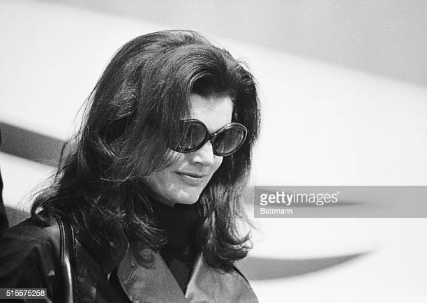 Jacqueline Kennedy Onassis, wearing dark glasses and black leather coat over a black outfit, leaves her chartered Olympic Airlines plane after...