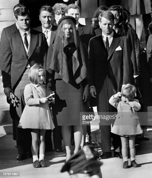 Jacqueline Kennedy stands with her two children Caroline Kennedy and John F Kennedy Jr and brothersin law Ted Kennedy and Robert Kennedy at the...