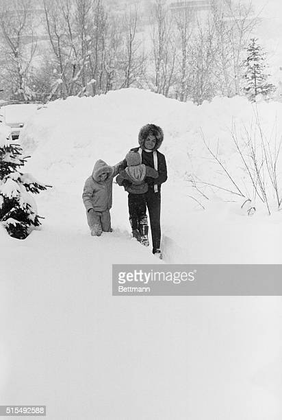 Jacqueline Kennedy struggles to carry son John through deep snow while daughter Caroline attempts to lend support The family spent a holiday at the...