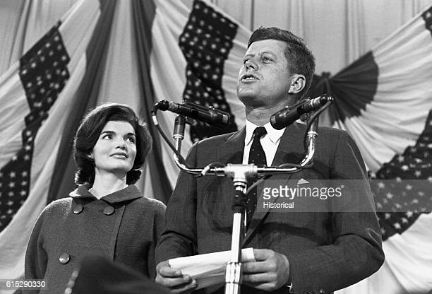 Jacqueline Kennedy watches as husband John F Kennedy speaks into several microphones in front of a back drop of flags Kennedy was the 35th president...