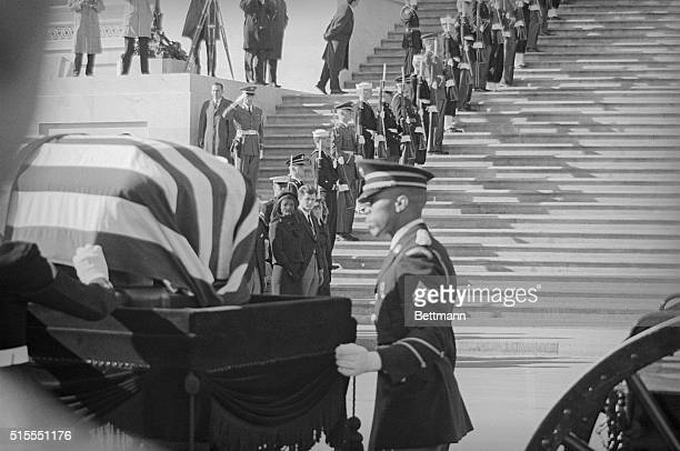 Jacqueline Kennedy with relatives watches solidiers load her husband's casket on caisson for his funeral at the US Capitol