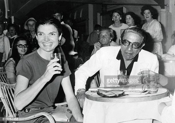 Jacqueline Onassis and her husband, Aristotle, have a drink at a cafe 6/23. The couple is on a cruise of the Mediterranean.