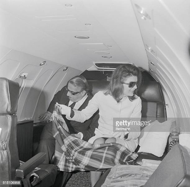 Jacqueline Onassis protects her husband Aristotle Onassis and herself from the cold with a lap rug as they sit in their private jet here march 7th...
