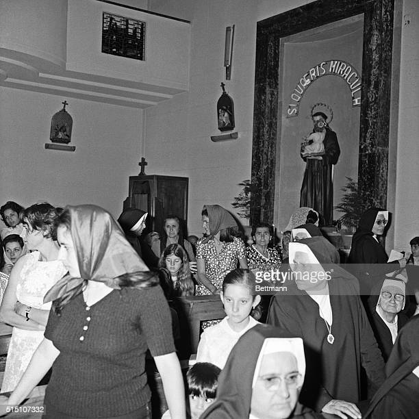 Jacqueline Onassis smilingly talks to a nun in the small church of the St Anthony Orphanage She is accompanied by her daughter Caroline Kennedy...