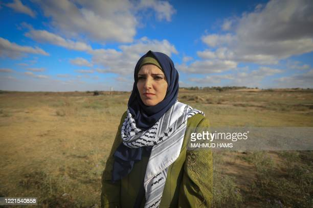 Jacqueline Shahada, who lost her left eye, stands at the place where she was shot in Bureij refugee camp in central Gaza, on May 28 , 2020. - Along...
