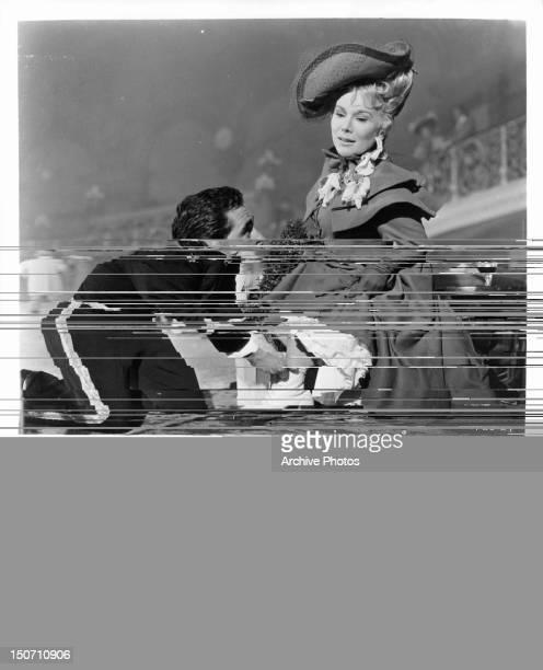 Jacques Bergerac adjusting skate of Eva Gabor in a scene from the film 'Gigi' 1958