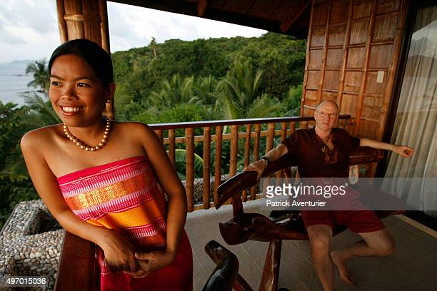 Jacques Branellec at his house on Taytay Island, with the manageress, who is wearing a golden pearl necklace. He has arrived to inspect the new...