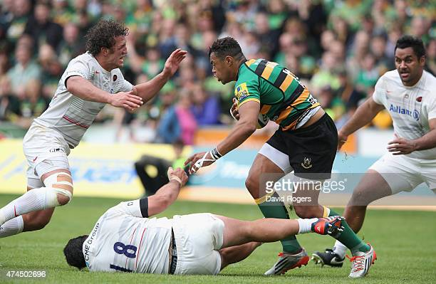 Jacques Burger and Juan Figallo of Saracens tackle Luther Burrell during the Aviva Premiership play off semi final match between Northampton Saints...