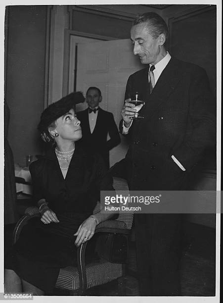 Jacques Cousteau the French oceanographer and underwater explorer who invented the Aqualung diving apparatus talks to his wife at a party
