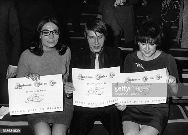 Jacques Dutronc, ayant reçu le prix Pierre-Brive Consécration, avec Nana Mouskouri et Régine, montrent leurs diplômes de l'académie Charles Cros le...
