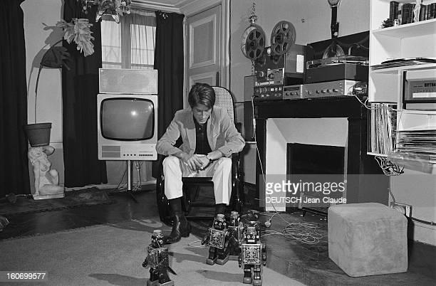Jacques Dutronc On The Cutting Edge Of Technology Attitude de Jacques DUTRONC assis sur un rockingchair regardant ses robots évoluer au milieu de son...