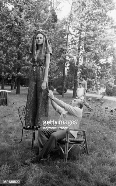 Jacques Esterel faisant des essayages avec une robe du soir et un pantalon à lames en 1969 France