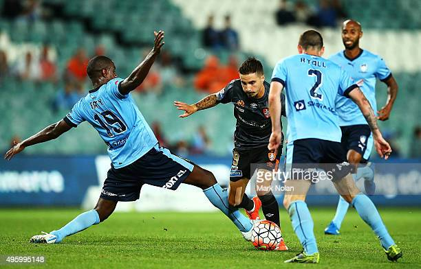 Jacques Faty of Sydney attempts to tackle Jamie Maclaren of the Roar during the round five ALeague match between Sydney FC and Brisbane Roar at...