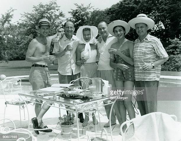 Jacques Fray, Jay Rutherford, Mr and Mrs Francis T. Hunter and Mr Angier Biddle Duke holding cocktail glasses on a pool deck, Southampton, NY, c 1955