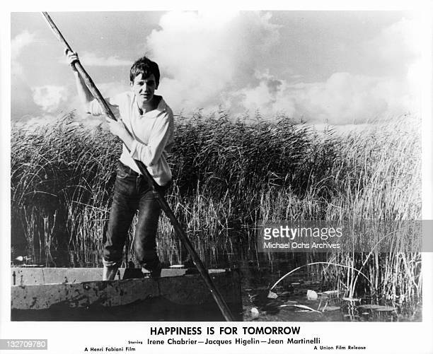 Jacques Higelin rowing raft through tall marsh in a scene from the film 'Happiness Is For Tomorrow' 1961