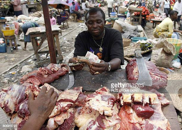 Jacques Lhuillery A meat seller counts his money with blood stained hands in a Lagos market on April 15 2008 In Nigeria where officials are keen to...