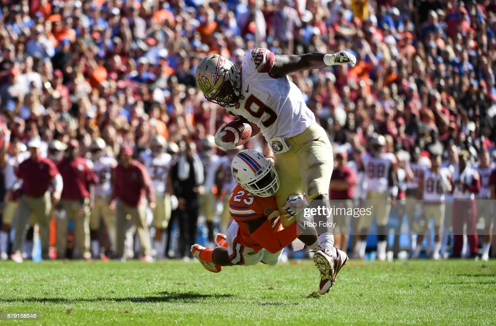 Jacques Patrick #9 of the Florida State Seminoles is tackled by Chauncey Gardner Jr. #23 of the Florida Gators during the first half of the game at Ben Hill Griffin Stadium on November 25, 2017 in Gainesville, Florida.