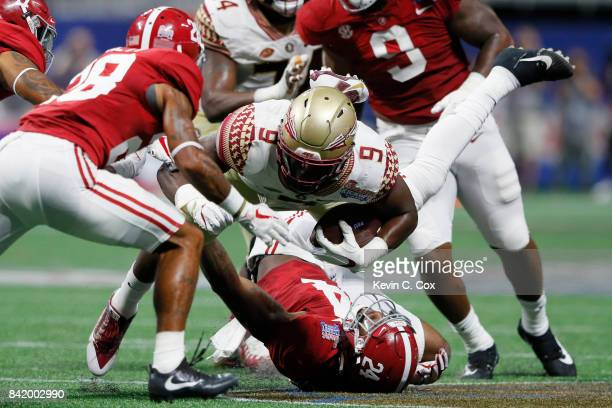 Jacques Patrick of the Florida State Seminoles is upended by Terrell Lewis of the Alabama Crimson Tide during their game at Mercedes-Benz Stadium on...