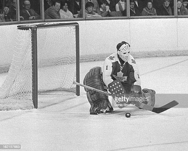 Jacques Plante of the Toronto Maple Leafs blocks the puck during a game at the Montreal Forum circa 1971 in Montreal Quebec Canada