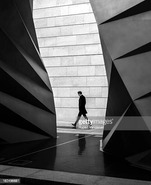Jacques Tati or undertaker style man walks, with hands in pockets between two sculptures and mirrors their curves and geometric shapes with his...