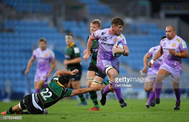 Jacques Vermeulen of Exeter Chiefs makes a break past Alex Mitchell of Northampton Saints to score his side's fifth try during the Heineken Champions...