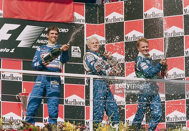 Jacques Villeneuve of Canada sprays champagne to celebrate with second placed Damon Hill and third placed Johnny Herbert after winning the Hungarian...
