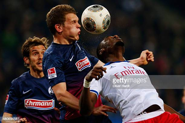 Jacques Zoua of Hamburg and Matthias Ginter of Freiburg compete for the ball during the Bundesliga match between Hamburger SV and SC Freiburg at...