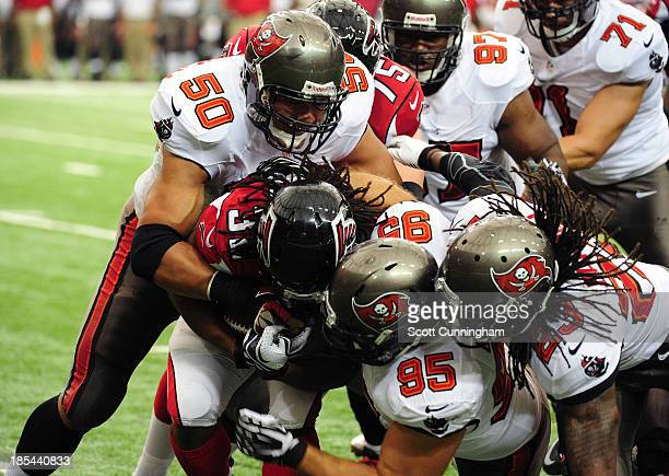 Jacquizz Rodgers of the Atlanta Falcons is tackled by Daniel Te'oNesheim Gary Gibson and Mark Barron of the Tampa Bay Buccaneers at the Georgia Dome...