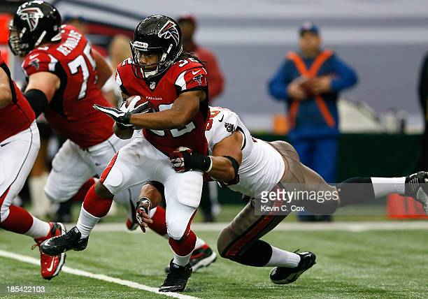 Jacquizz Rodgers of the Atlanta Falcons rushes against Daniel Te'oNesheim of the Tampa Bay Buccaneers at Georgia Dome on October 20 2013 in Atlanta...