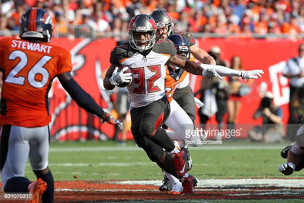 Jacquizz Rodgers of the Bucs runs the ball thru the Broncos defense during the NFL game between the Denver Broncos and Tampa Bay Buccaneers on...
