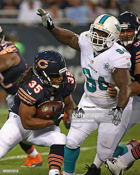 Jacquizz Rodgers of the Chicago Bears is chased by CJ Mosley of the Miami Dolphins during a preseason game at Soldier Field on August 13 2015 in...