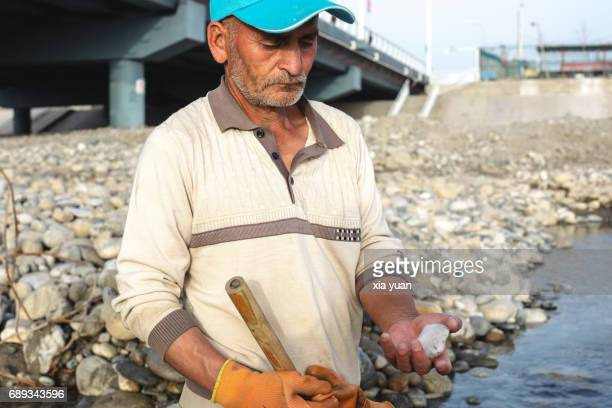 A Jade digger carefully checking the stone dug from the riverbed of Yurungkash River,Hotan,China