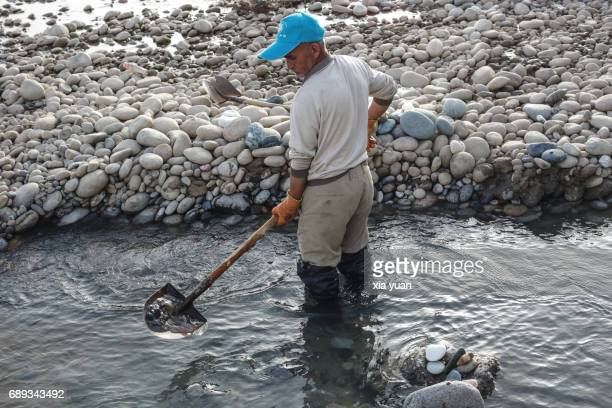 A Jade digger digging for jade on the riverbed of Yurungkash River,Hotan,China