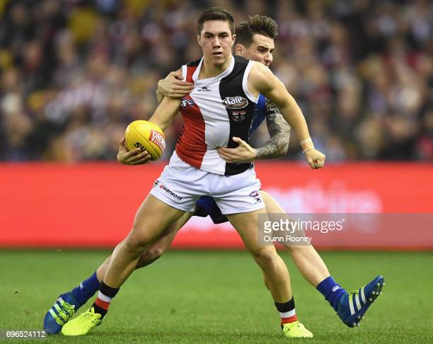 Jade Gresham of the Saints handballs whilst being tackled Aaron Mullett of the Kangaroos during the round 13 AFL match between the North Melbourne...