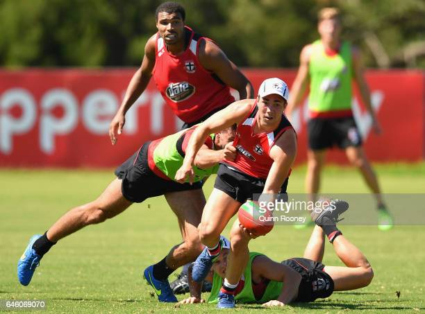 Jade Gresham of the Saints handballs whilst being tackled during a St Kilda Saints AFL training session at Linen House Oval on February 28 2017 in...