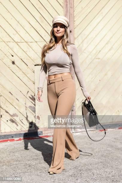 Jade Tuncdoruk wearing a Lack Of Colour hat Style Addict top Zara pants and a YSL handbag at MercedesBenz Fashion Week Resort 20 Collections on May...